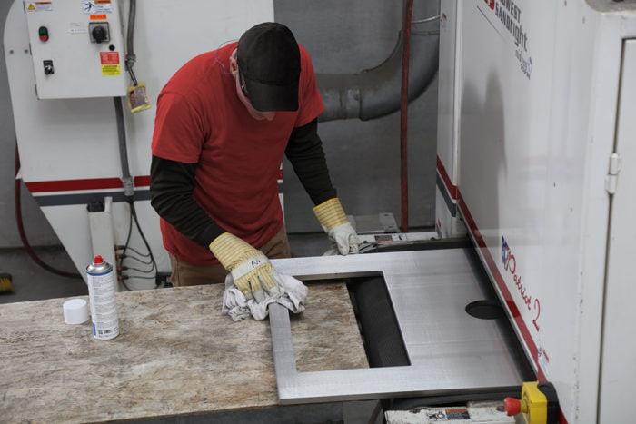 employee polishing steel on machine