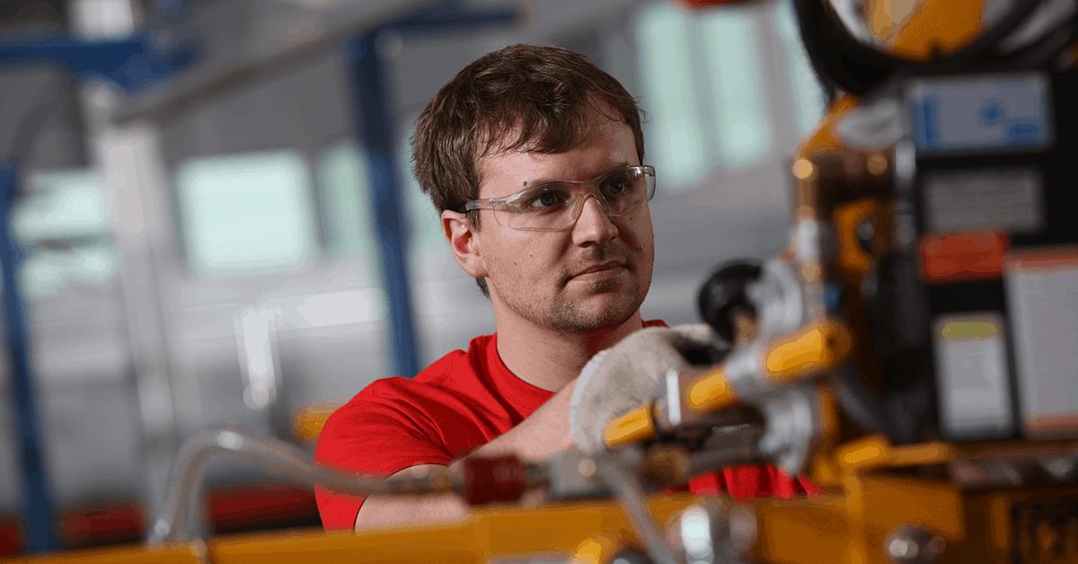 Emtek employee working on machinery